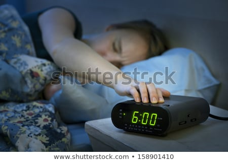 young-woman-pressing-snooze-button-450w-158901410